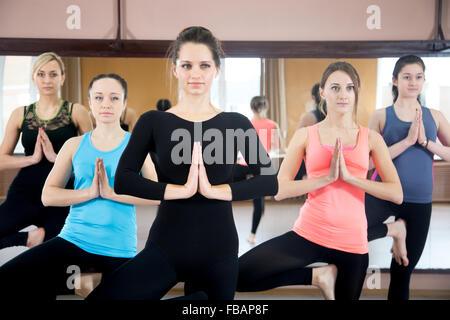 Sporty yogi girls in class in Yoga pose vrikshasana (Vriksasana or Tree Pose) using namaste - Stock Photo