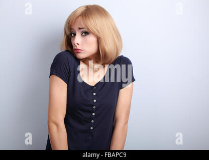 Confused young casual woman with blond hair on blue background - Stock Photo