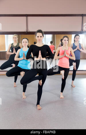 sporty yoga girls in class exercise sitting in ardha