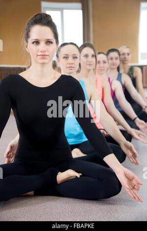 sporty yogi girls doing fitness exercises in class