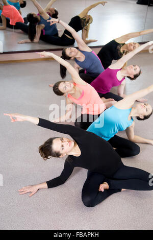 Team of sporty yogi girls in class in Yoga pose, sitting cross-legged, bending, doing exercises for abs, waist and - Stock Photo