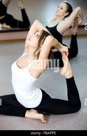 Sporty Yogi Girls doing yoga exercises backbends in class, sitting in asana eka pada radzhakapotasana (One-Legged - Stock Photo