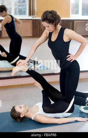 Yogatheraphy. Beautiful young females practicing yoga therapy, doing exercises in class, instructor assists to yogi - Stock Photo