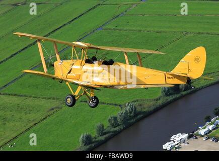 A de Havilland Tiger Moth bi-plane over the Dutch countryside - Stock Photo