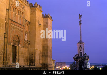 Cordoba.Andalusia. Spain: At left Mosque-cathedral´s walls and Triumph of San Rafael at right, in Torrijos street - Stock Photo