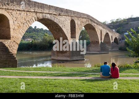 Couple sitting near the Medieval bridge in Puente La Reina - Navarre, Spain. - Stock Photo