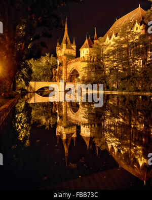 View of the Entrance Gate , Tower and Bridge of the Vajadahunyad Castle reflected in a a Lake at Night, Budapest, - Stock Photo
