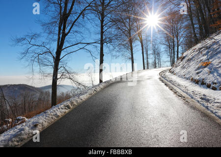 Empty road in winter with sun beam in the sky - Stock Photo
