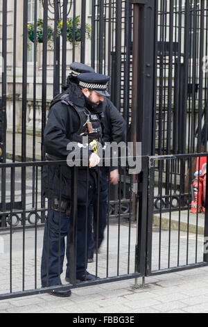 Armed Police officers shutting the gates at 10 Downing street - Stock Photo