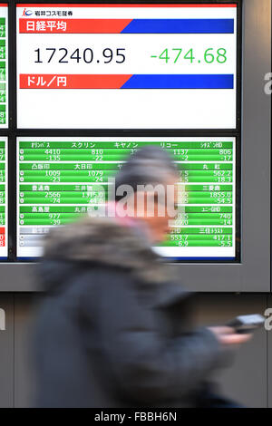 Tokyo, Japan. 14th January, 2016. A man walks past a signboard indicating Japanese share prices on January 14, 2016 - Stock Photo