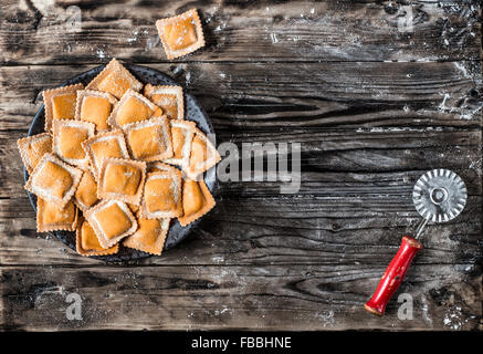 Ravioli di zucca. Homemade fresh pumpkin ravioli on a wooden table and a vintage cutter pasta. - Stock Photo