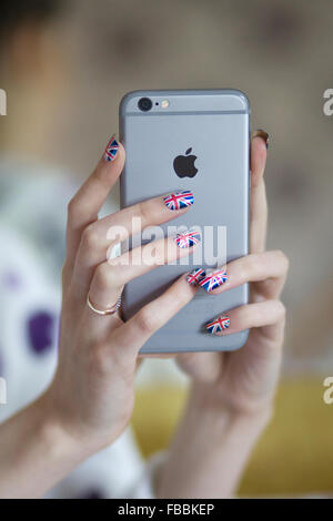 Hands holding a Apple i Phone with nails painted in the union jack - Stock Photo