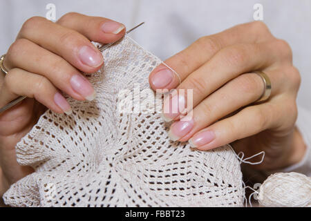 crochet woman crafting making knitting pattern knitted handmade lace detail stitch texture beige yarn openwork hands - Stock Photo