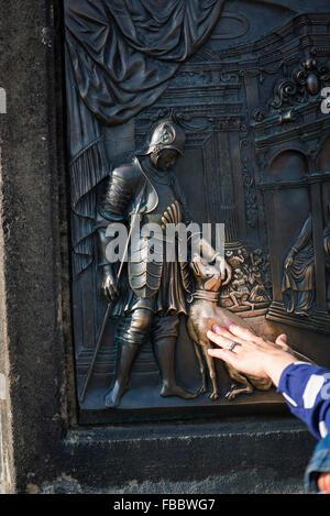 Tourist touches dog on Bronze below the statue of St, John of Nepomuk on Charles bridge, Prague, Czech Republic - Stock Photo