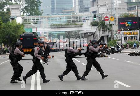 Jakarta, Indonesia. 14th Jan, 2016. Indonesian police take position and aim their weapons as they pursue suspects - Stock Photo