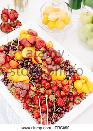 White plate with fruits and berries on table outdoor - Stock Photo