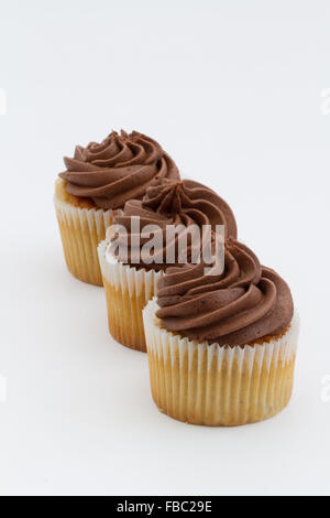 Three chocolate cupcakes in a row on an isolated white background. Portrait orientation. - Stock Photo