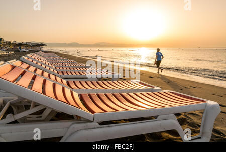 An early morning jogger runs along Torremolinos beach on the South Coast of Spain past a row of sun loungers. - Stock Photo