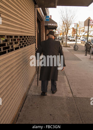 Welldressed elderly man walking along with a cane for extra support and balance on Church Avenue in Brooklyn, NY. - Stock Photo