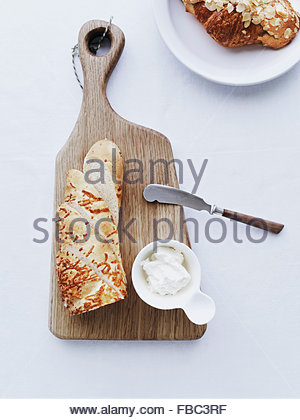Baguette on cutting board served with cream cheese - Stock Photo