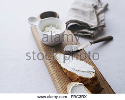 Bread on cutting board served with cream cheese - Stock Photo