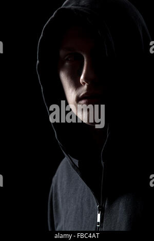 Portrait of mysterious man in hoodie in the dark, dangerous criminal scarcely visible in the dusk - Stock Photo