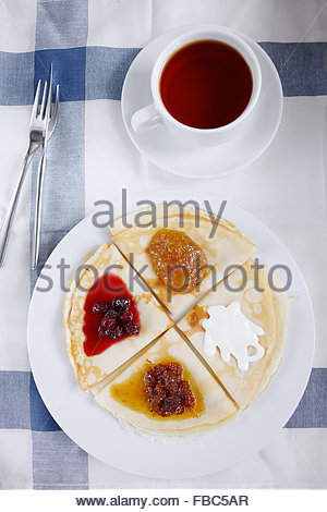 Overhead view of breakfast table setting of berry crepes and black tea - Stock Photo