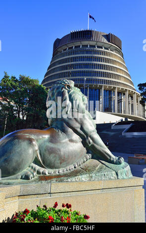 one of the two bronze lions on  Wellington s cenotaph with Parliament (Beehive) behind , central Wellington   New - Stock Photo