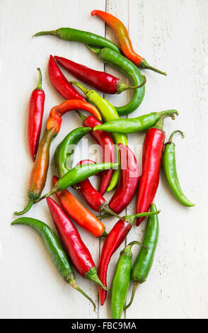 Red, Green and Orange Hot Chilli Peppers on White Wooden Background - Stock Photo