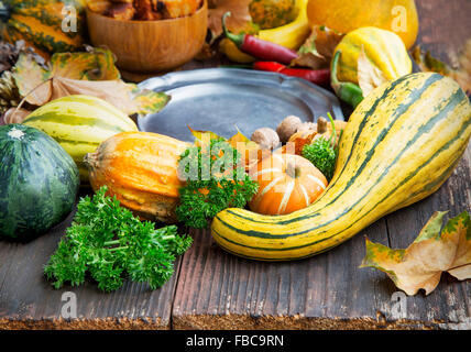 Autumn Decorations with Pumpkins, Dried Leaves, Chestnuts and Acorns in Wooden Background - Stock Photo