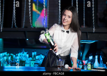 Beautiful cheerful brunette bartender girl in white shirt and black bow tie, serving alcohol drink at bar counter, - Stock Photo