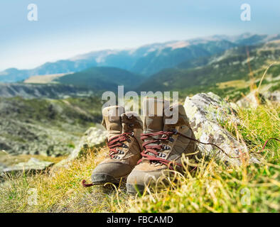 Mountain Hiking Boots in the Summer Grass Outdoor - Stock Photo