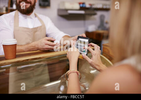 Young woman paying for coffee by credit card at coffee shop. Focus on woman hands entering security pin in credit - Stock Photo