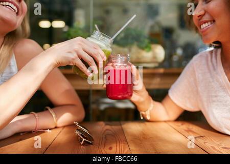 Close up shot of female friends toasting juice glasses at sidewalk cafe. Two happy women enjoying fresh drinks at - Stock Photo