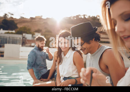 Outdoor shot of happy young man sitting by the pool with his friends partying. Group of young people hanging around - Stock Photo