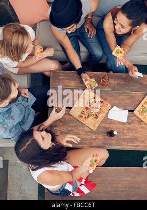 Top view of group of young people having drinks and pizza at party. Multiracial friends hanging out together. - Stock Photo