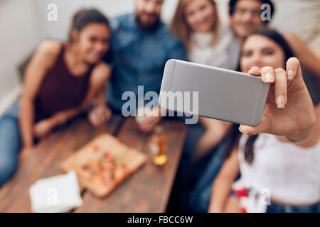 Young people in a party taking self portrait with mobile phone. Focus on smart phone in woman's hand. Group of young - Stock Photo