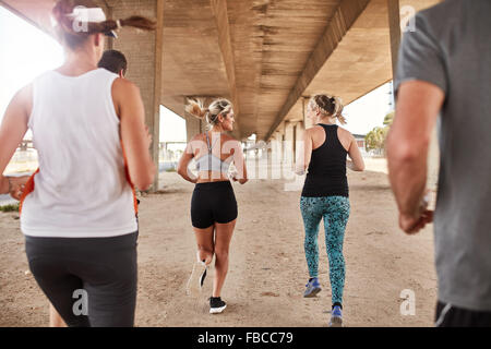 Portrait of group of runners in fitness clothing running under a bridge. Young men and women running together. - Stock Photo