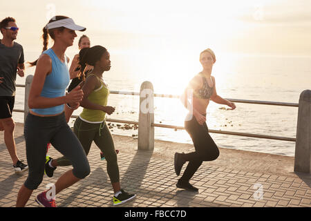 Young people running along seaside at sunset. Closeup image of group of runners working out on a road by the sea. - Stock Photo