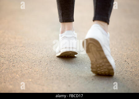 Female feet in white sneakers running on concrete, jogger practicing, close-up. Healthy, active lifestyle concepts, - Stock Photo