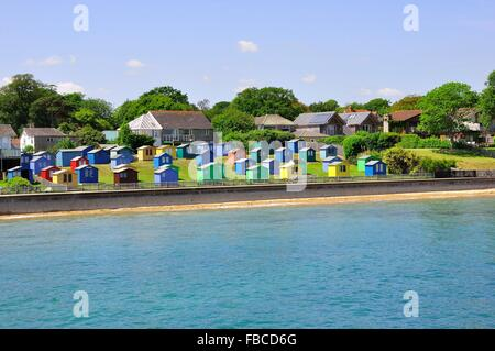 Brightly coloured beach huts on the seafront at Bembridge, Isle of Wight - Stock Photo