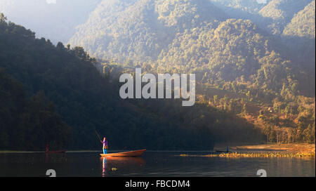 Nepalese woman poling boat Phewa Lake, Pokhara Nepal - Stock Photo