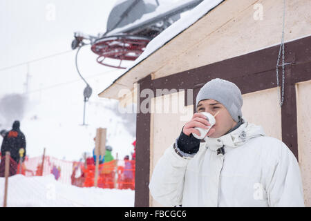 Young man drinking a cup of hot coffee to warm up as he takes a break from skiing at a mountain resort in winter - Stock Photo
