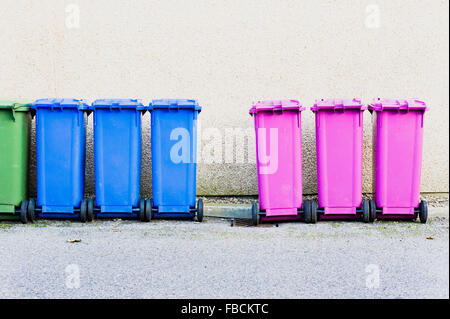 A row of plastic waste bins for collection in front of a stone wall - Stock Photo