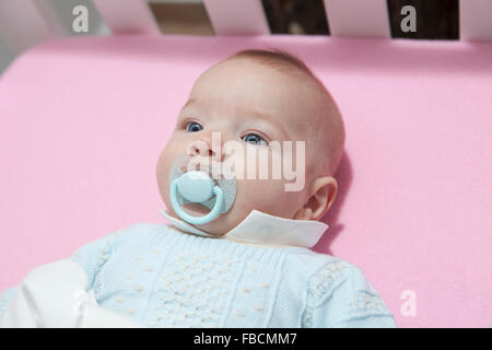 Awake four month baby boy lying in cot with pacifier. Uphead view - Stock Photo