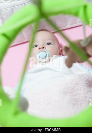 Awake four month baby boy lying in white cot with mobile. Overhead view - Stock Photo