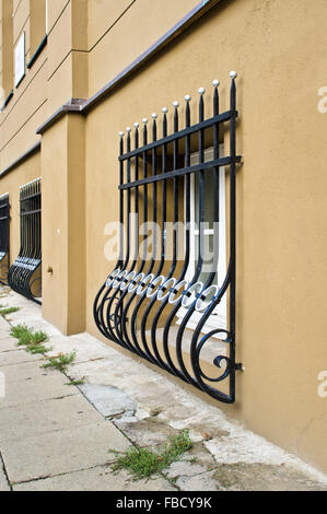 Wrought iron window bars on the exterior of an urban building at street level - Stock Photo