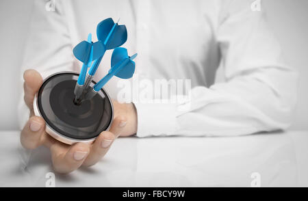 Man hand holding a target with three darts hitting the center over white background. Concept of personal coaching - Stock Photo