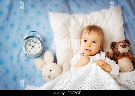One year old baby with alarm clock - Stock Photo