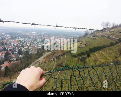 Cropped Image Of Person Hand Holding Chainlink Fence In Front Of Green Hill - Stock Photo
